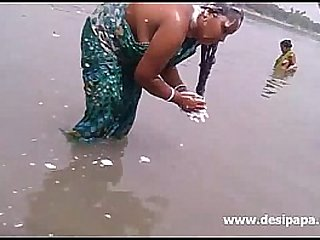 chubby indian girl washing hair in the river